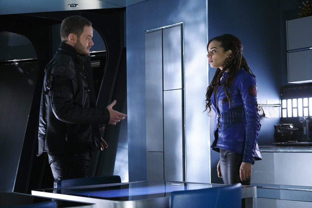 "KILLJOYS -- ""Dutch and the Real Girl"" Episode 201 -- Pictured: (l-r) Aaron Ashmore as John, Hannah John-Kamen as Dutch -- (Photo by: Steve Wilkie/Syfy/Killjoys II Productions Limited)"